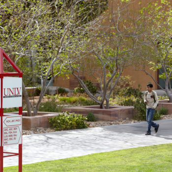 A student walks across the campus of UNLV