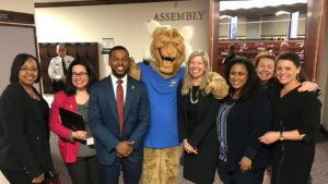 Assembly members Monroe-Moreno, Cohen, McCurdy II, Krasner, Miller, Bilbray-Axelrod and Benitez-Thompson with the WNC Wildcat.