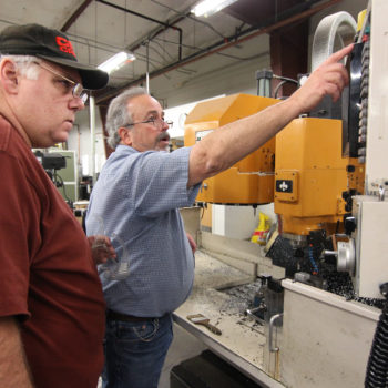 Instructor Paul Eastwood helps Bret Grouse with the CNC (computer numerical control) device in machine class at Western Nevada College