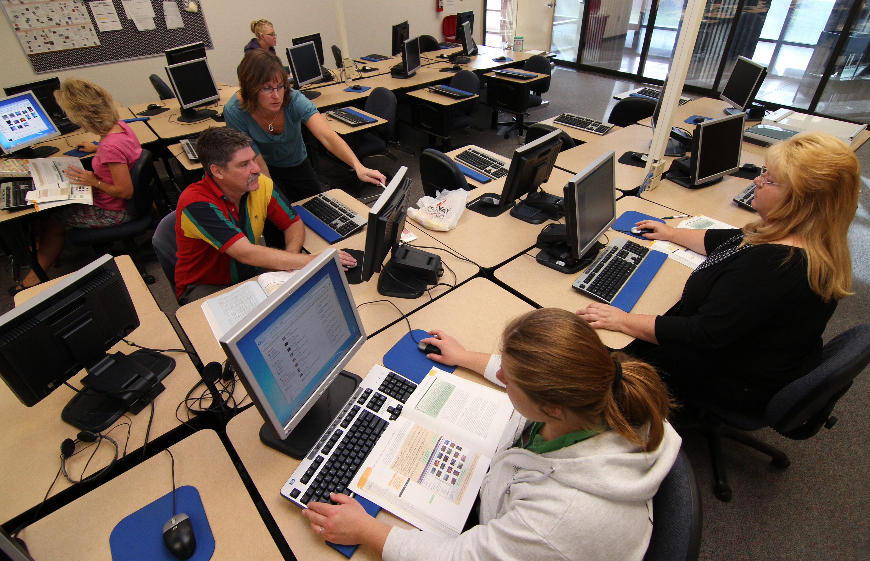 An instructor works with students in a computer class at WNC