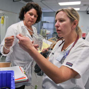Western Nevada College nursing instructor Catherine Fuller, R.N., center, evaluates student Carrie Garrett during a lab exercise