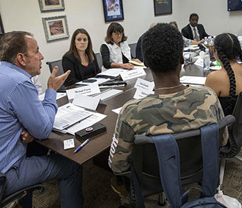 Members of NSHE and foster youth students engage in a round table discussion in a conference room.